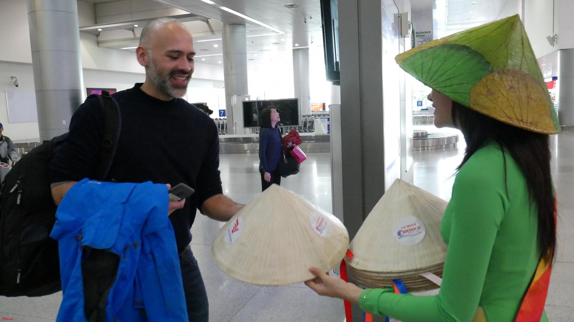 Du khách được chào đón trong ngày đầu năm mới và được tặng quà lưu niệm là chiếc nón lá.