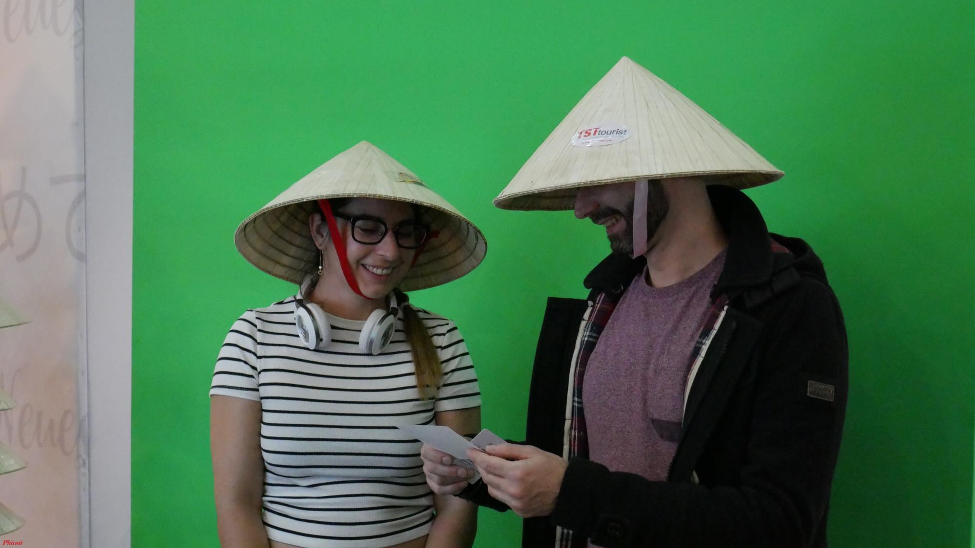 Du khách thích thú với việc được chụp hình lưu niệm tại sân bay và được tặng chiếc nón lá.