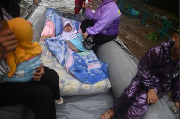 Một phụ nữ lớn tuổi tại khu vực Depok, nam Jakarta được gia đình đưa đi khỏi nơi ở để tránh lụt - Ảnh: Reuters.