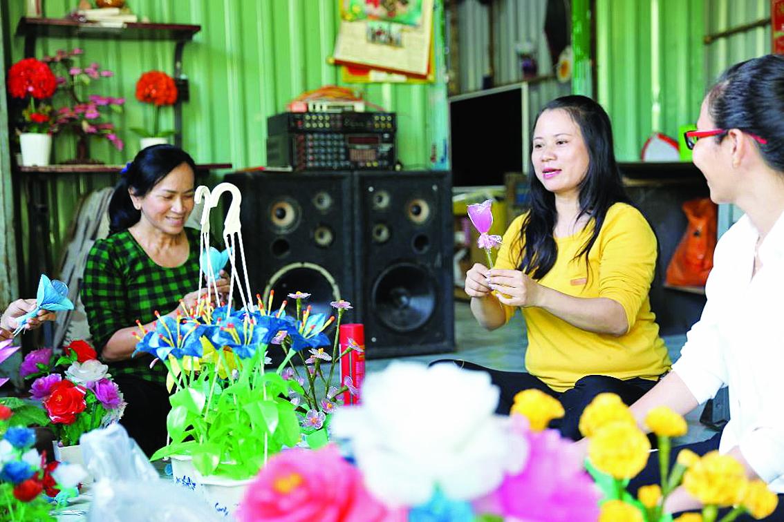 Chị Nguyễn Thị Nhuyễn (giữa) đang giới thiệu cách làm hoa ni-lông cho chị em phụ nữ các ấp của xã Bình Khánh