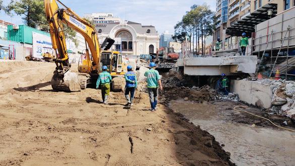 Các công nhân đang thi công hoàn trả lại mặt bằng công viên phía trước Nhà hát TPHCM - Ảnh: TTO