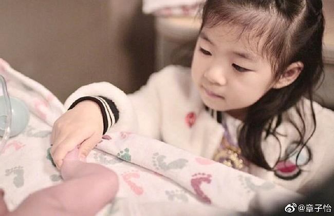 Uông Phong và con gái cưng nựng em bé mới chào đời.
