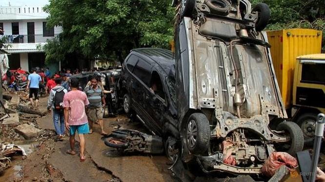 Những chiếc xe chất chồng lên nhau ở Bekasi khi nước rút dần và người dân quay về.