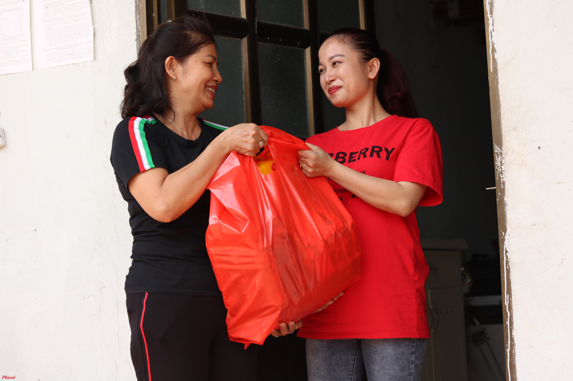 Chị Bên (bìa trái) trao quà Tết cho chị em ở trọ.