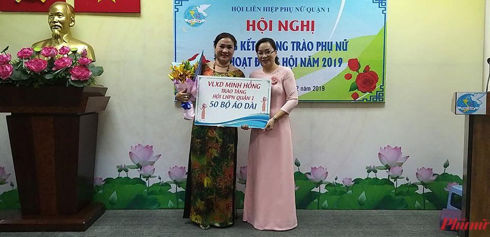 Bà Hoàng Thị Thu Liên- Chủ tịch Hội LHPN Quận 1(bên phải) nhận 50 bộ áo dài của nữ doanh nghiệp trao tặng Hội, sẻ chia với chị em