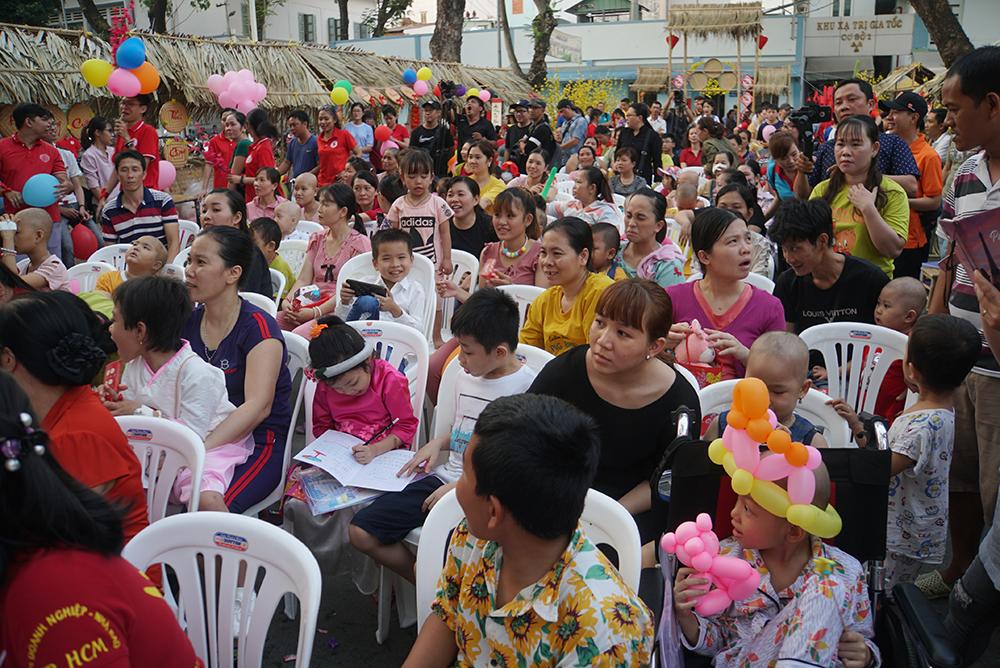 Các bé dưới sân cũng có quà gồm sữa, bánh, bao lì xì 500.000 đồng, và tập trung xem văn nghệ chào xuân.