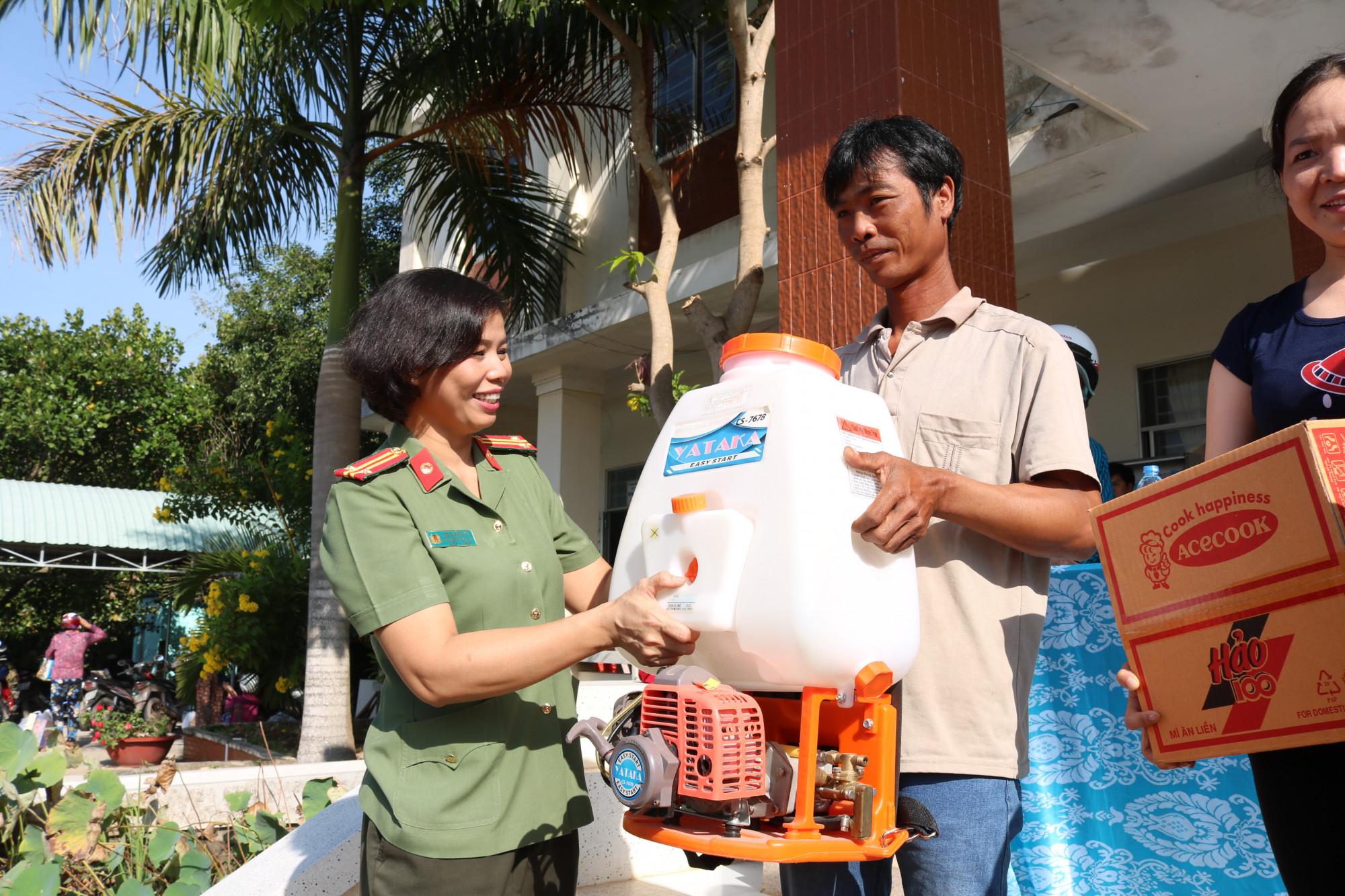 Trung tá Cao Thị Hồng Tươi - Chủ tịch Hội Phụ nữ Công an TP.HCM - trao máy rải phân cho đại diện các hộ gia đình.