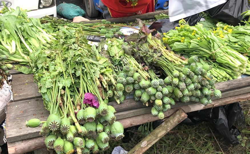 Những bó quả cây anh túc được bày bán ngay bên cạnh những bó rau xanh