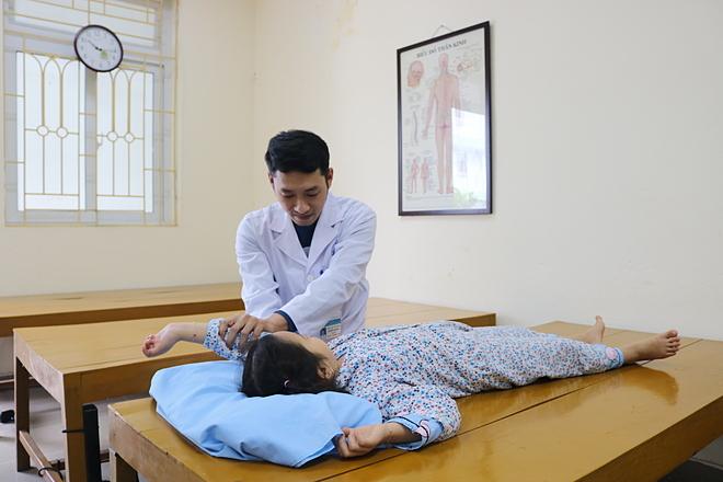 Bác sĩ tập các bài phục hồi chức năng cho cháu bé. Ảnh: Nguyễn Tuyết