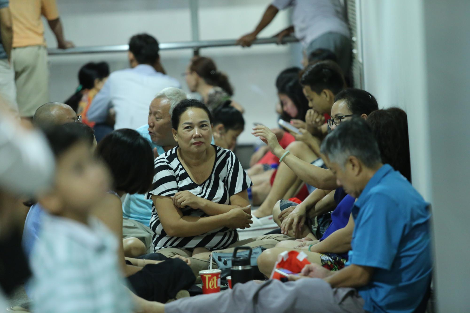 Không thể chen lấn giữa đám đông nên nhiều người chọn cách dời xa khu vực và ngồi bệt dưới sảnh nhà ga để chờ đợi chuyến bay đến