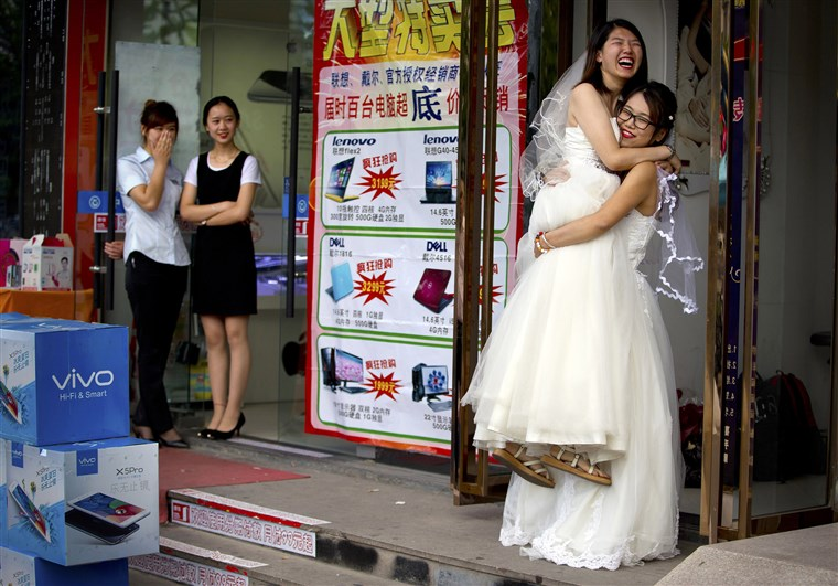 """Li Tingting hạnh phúc trong vòng tay của """"vợ"""" Teresa Xu bên ngoài một thẩm mỹ viện ở Bắc Kinh, nơi hai người đang chuẩn bị cho đám cưới không chính thức của mình. Ảnh chụp tháng 7/2015 - Ảnh: AP"""