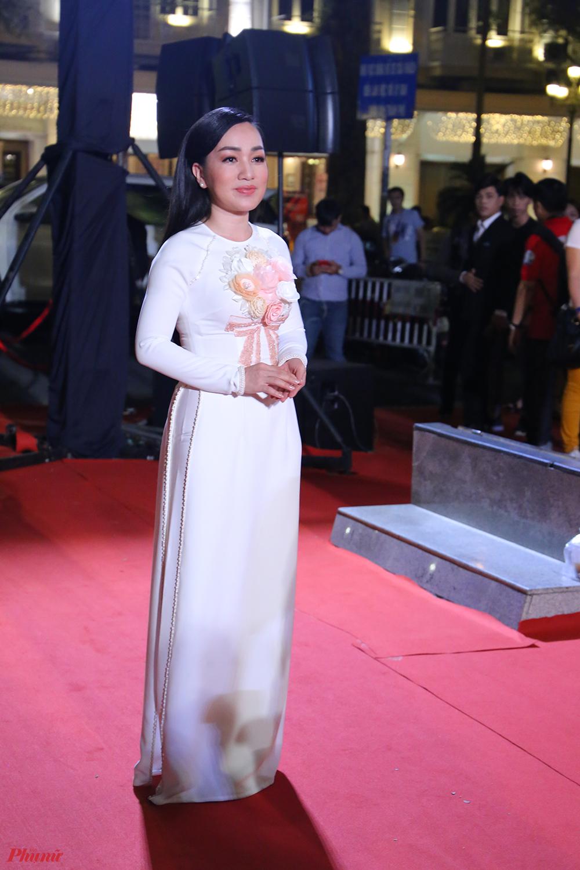 Ca sĩ Hà Vân trẻ trung với tà áo dài trắng đính hoa màu hồng nhạt.