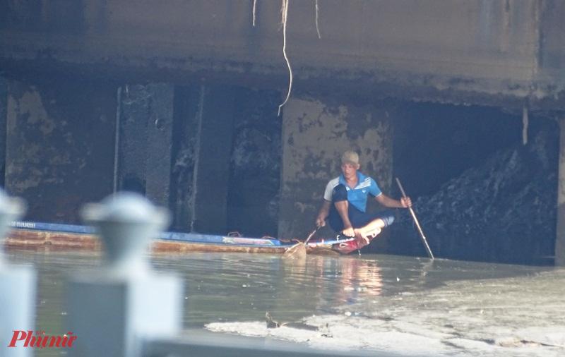 -Một thanh niên núp dưới gầm cầu để chích điện bắt cá để khó bị phát hiện. Ảnh: TRUNG THANH