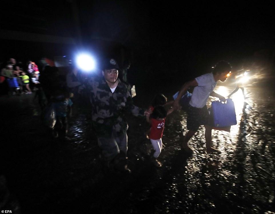 Cảnh sát giúp một cô bé vượt qua cơn mưa khi cư dân tranh nhau sơ tán khỏi nhà sau các hoạt động núi lửa