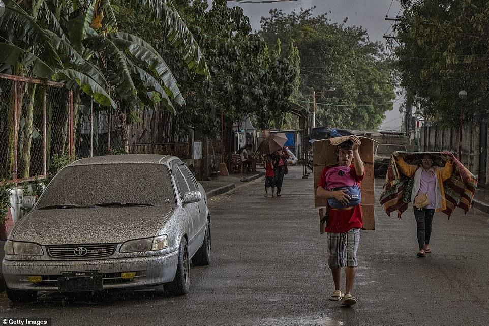 Người dân đi bộ dọc theo con đường phủ đầy tro trộn với nước mưa sau khi núi lửa bắt đầu phun tro, đá và hơi nước