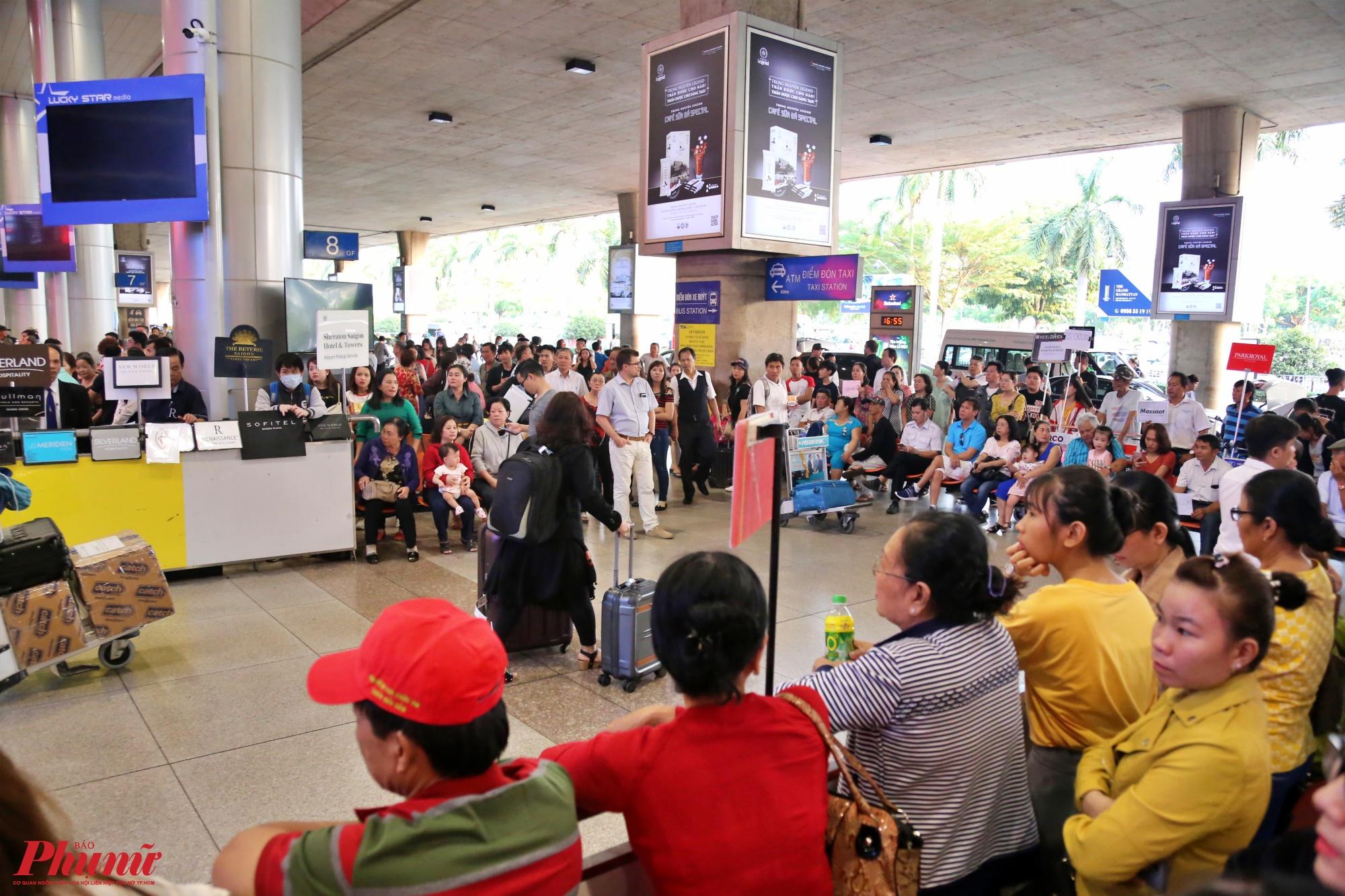 Người thân đứng chât kín ở cửa ra vào ở ga quốc tế để đợi đón người nhà