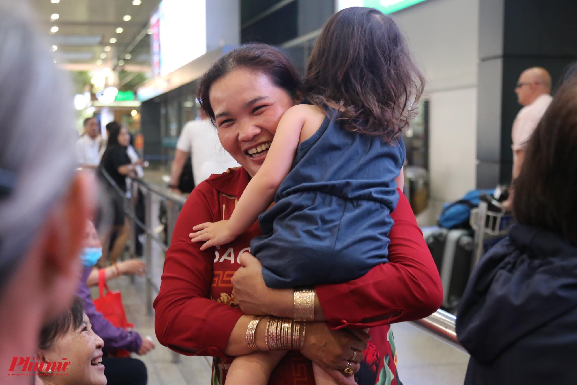 Chị Ngọc tươi cười ôm đứa cháu nhỏ ra xe để về quê ăn tết cùng gia đình