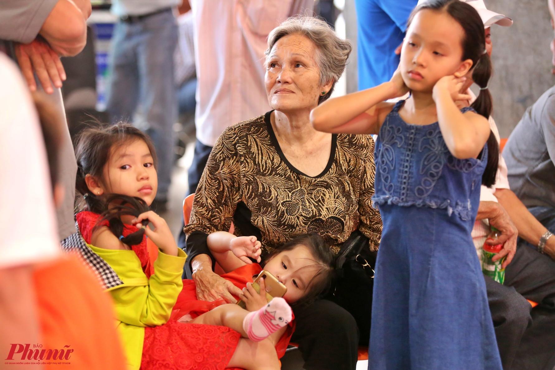 Một cụ bà nóng ruột ngồi ôm 2 đứa cháu nhìn lên bảng điện tử các chuyến bay đáp xuống nhà ga quốc tế