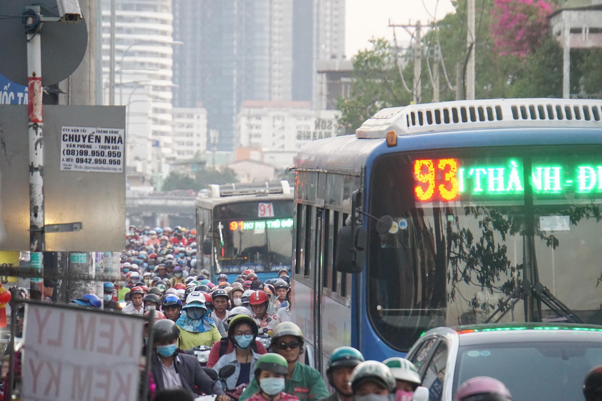 Xe buýt nối dài kẹt trong dòng xe máy đang bao vây
