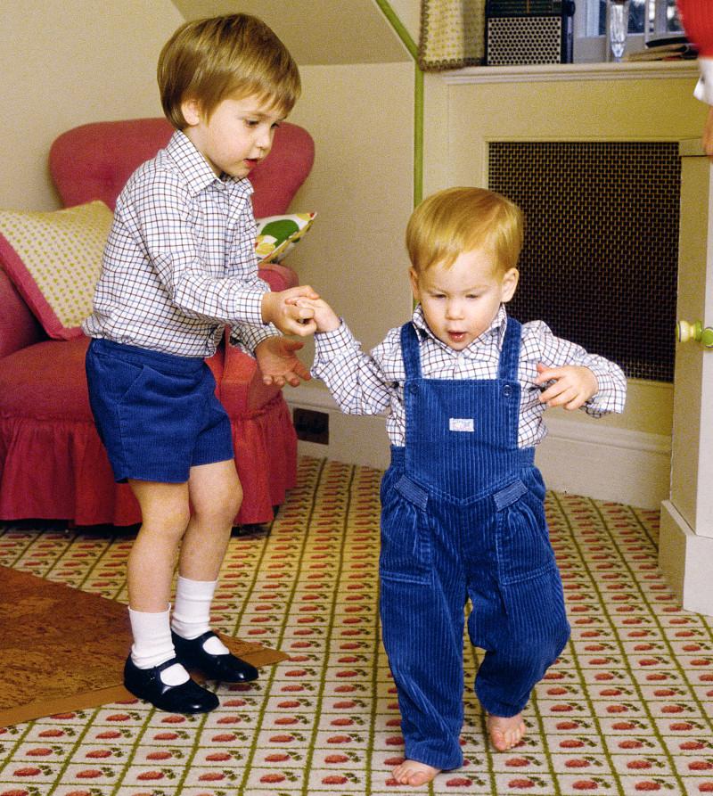 Hoàng tử William và Harry trông vô cùng đáng yêu khi diện trang phục đôi. Anh trai ân cần nắm tay em tập cho Harry những bước đi đầu tiên. Khoảnh khắc đáng nhớ này được ghi lại vào tháng 10/1985, khi Hoàng tử Harry được 13 tháng tuổi