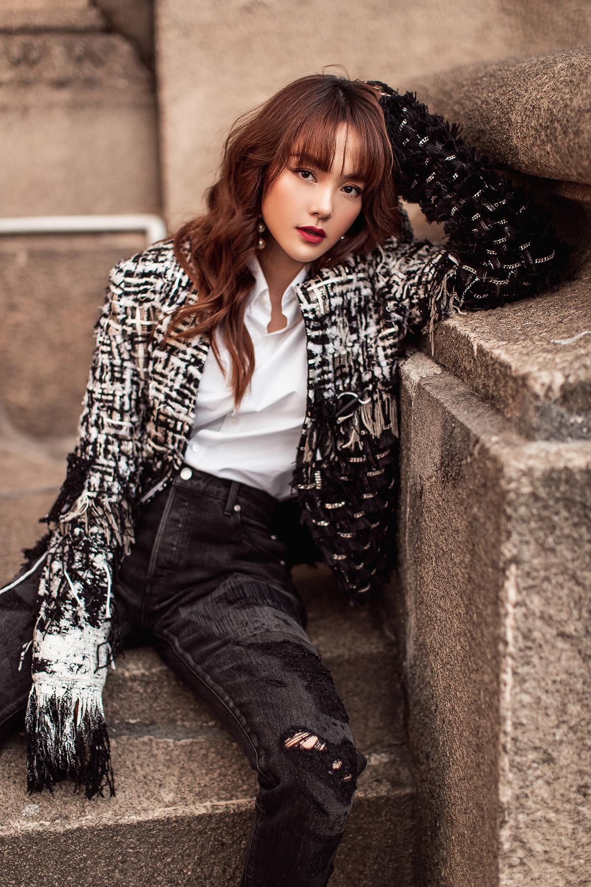 Sơ mi trắng, quần jeans đơn giản được Minh Hằng làm mới khi phối thêm cùng áo khoác vải tweed với hiệu ứng loang màu đậm, nhạt độc đáo.