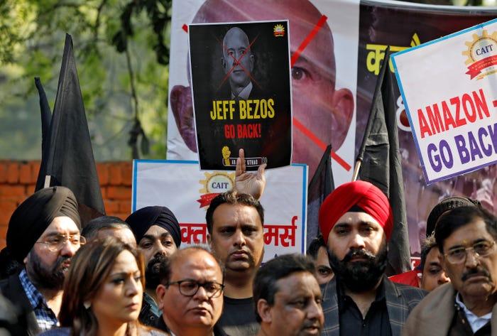 Các thành viên của Liên minh các thương nhân Ấn Độ giơ cao biển hiệu phản đối trong cuộc biểu tình hôm thứ Tư 15/1 tại New Delhi, chống lại chuyến thăm của tỷ phú Bezos.