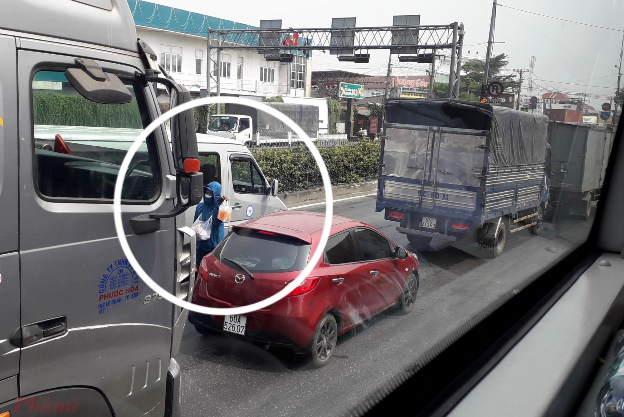 """Công việc bán nước giải khát dạo trên tuyến Quốc lộ 1A ở TPHCM được ví là nghề """"chặn đầu xe kiếm sống"""". Ảnh: Hoàng Nhiên."""