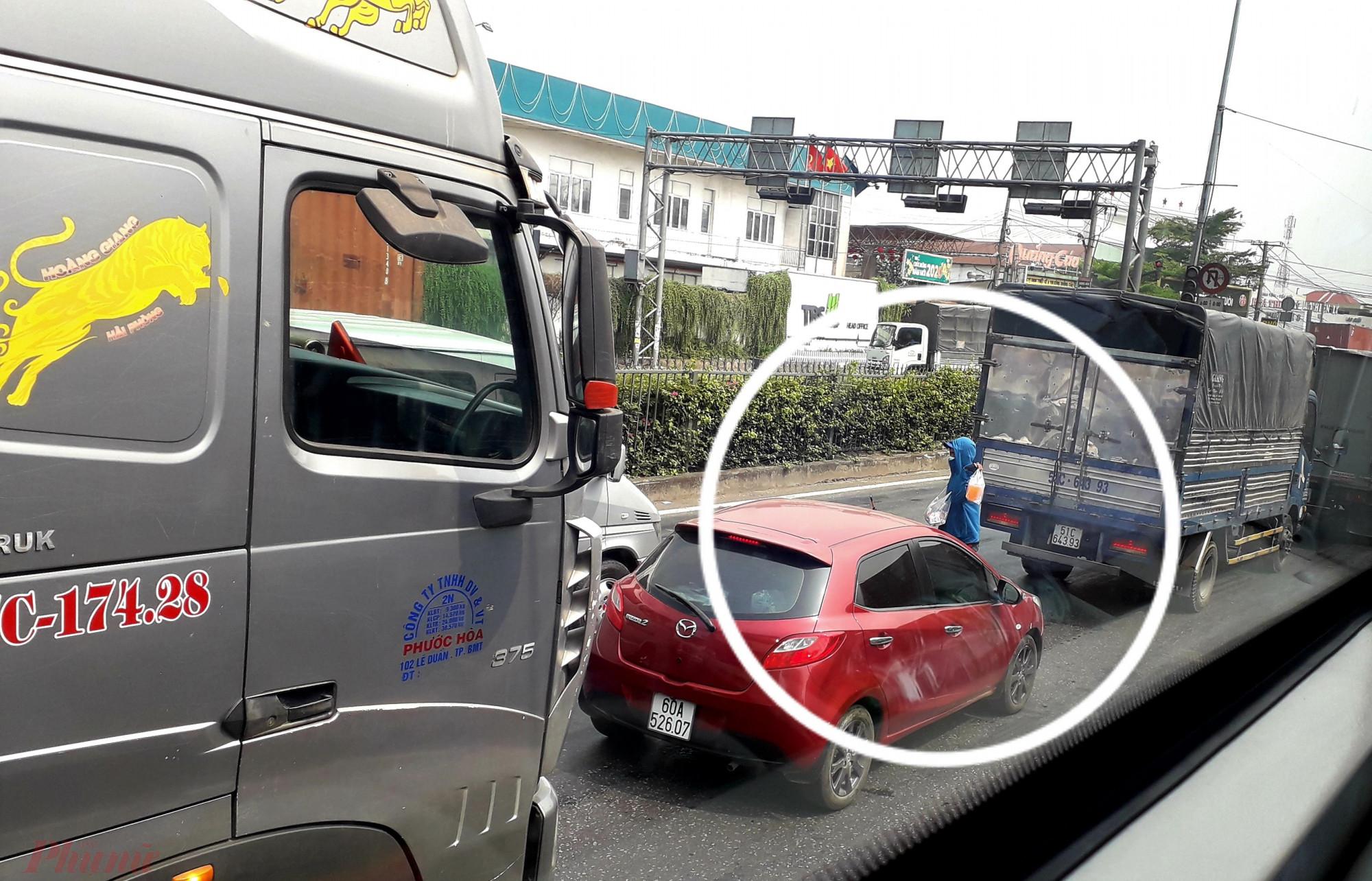 Nhiều người bán nước giải khát dạo len lỏi giữa dòng xe cộ ùn ứ trên Quốc lộ 1A để bán. Ảnh: Hoàng Nhiên.
