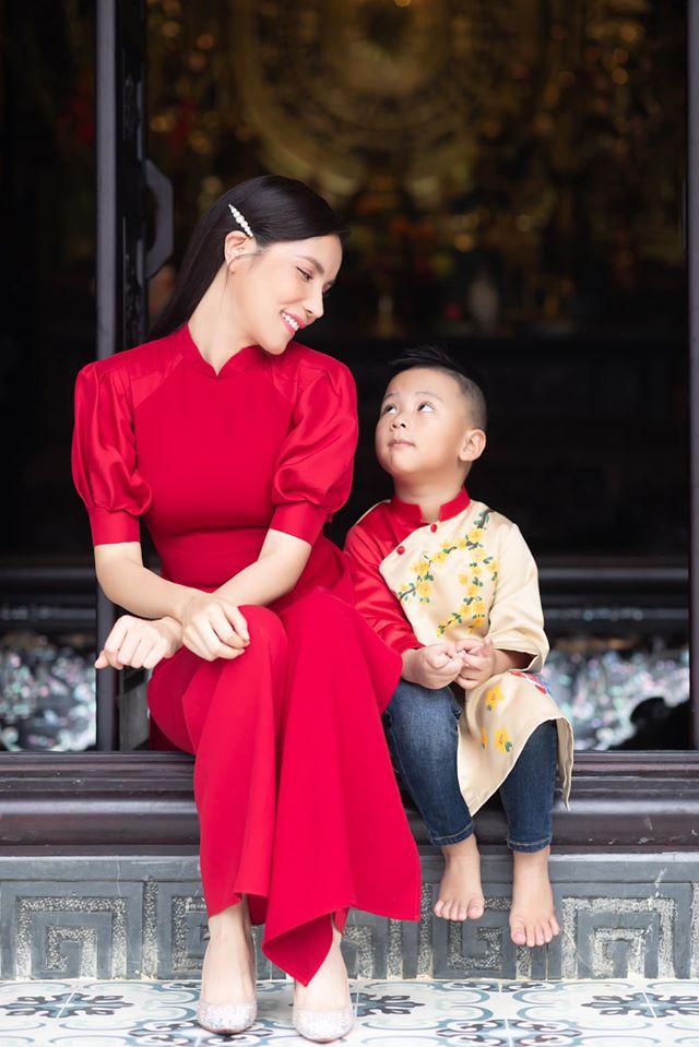 Ca sĩ Kiwi Ngô Mai Trang đưa con trai đi du xuân với những chiếc áo dài cách điệu trẻ trung, duyên dáng. Thiết kế giúp nữ ca sĩ trông trẻ hơn tuổi thật. Từ nhiều ngày trước, không khí đón Tết tại gia đình nữ ca sĩ đã trở nên rộn ràng với những hoạt động như trang trí nhà cửa, gói bánh chưng...