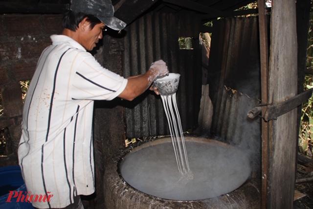 Công đoạn làm bún hoàn toàn thủ công. Trong ảnh: Người thợ đang ép bột qua muỗng để tạo thành những sợi bún.