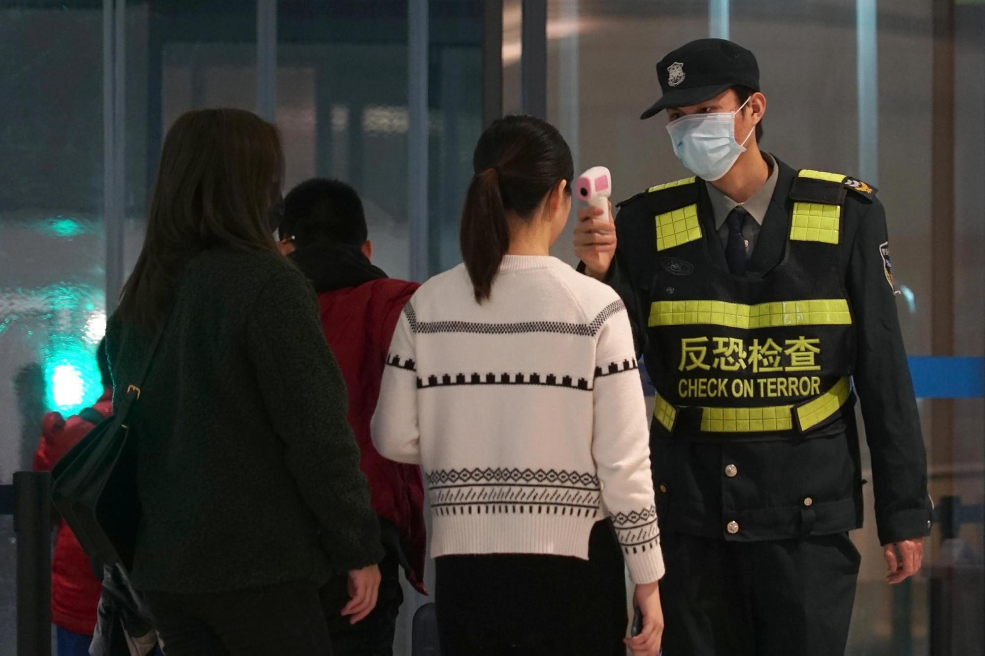 Nhân viên an ninh tăng cường kiểm tra nhiệt độ và sức khỏe hành khách tại các sân bay ở Trung Quốc.
