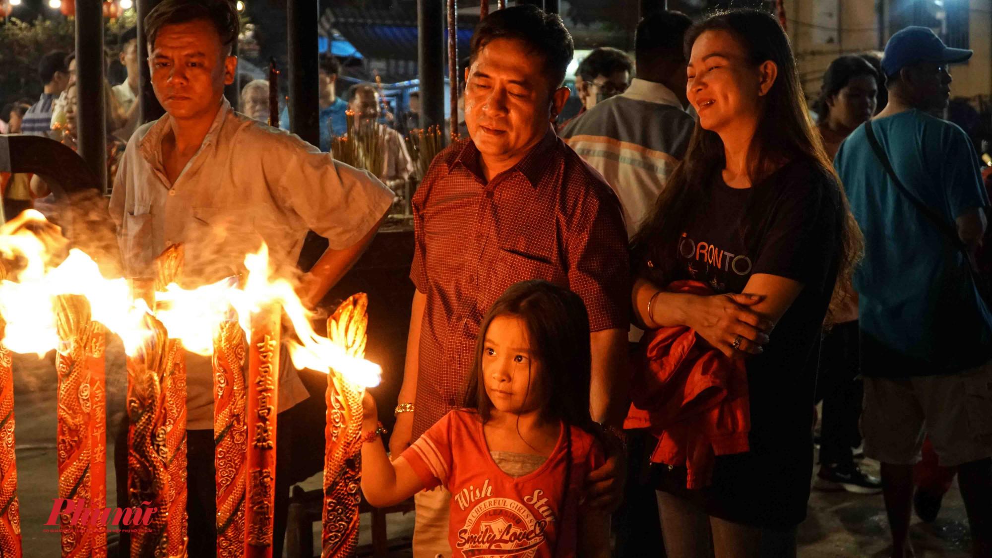 Gia đình nhỏ hướng dẫn con gái đốt nhang dịp đầu năm