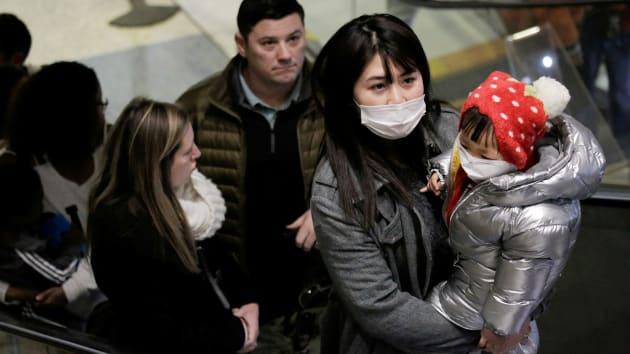 Một du khách đến từ Trung Quốc và con gái đeo khẫu trang khi hạ cánh xuống sân bay Seattle-Tacoma International Airport, bang Washington, Mỹ hôm 23/1.