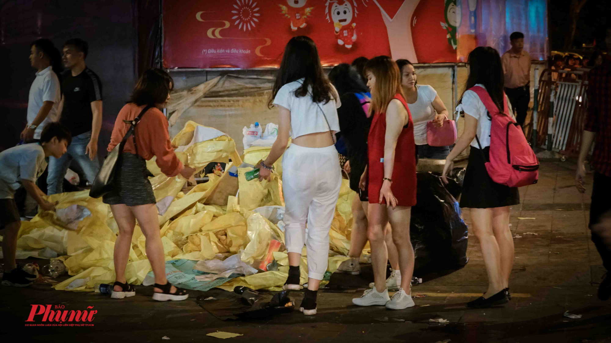 Nhóm bạn trẻ xusnh xính váy áo cũng nhanh chóng hỗ trợ nhặt rác