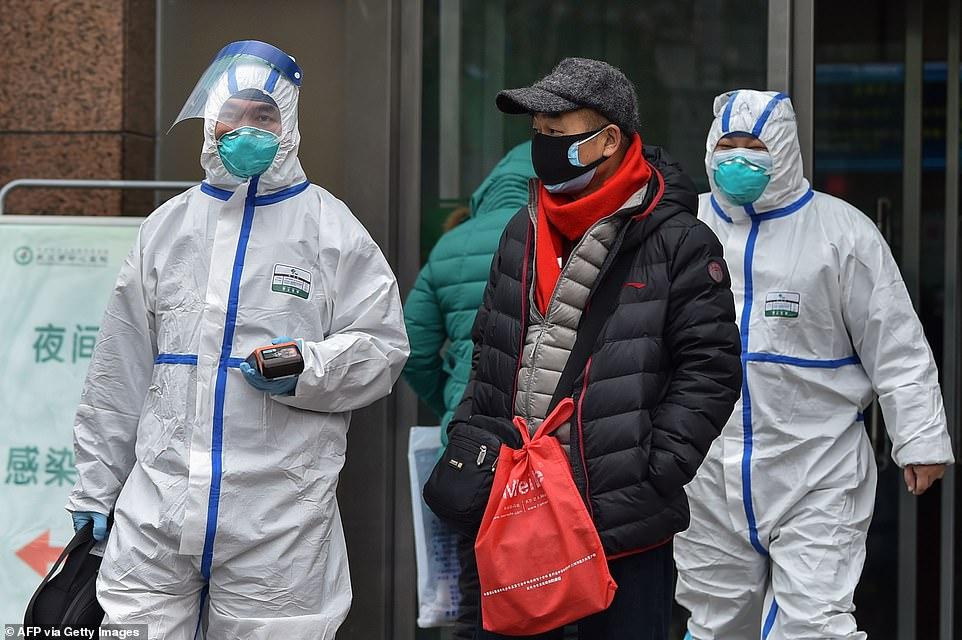 Nhân viên y tế mặc quần áo đặc biệt để bảo vệ chống lại coronavirus đi bộ bên ngoài bệnh viện ở Vũ Hán.