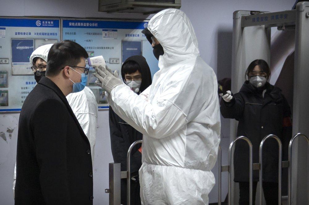 Nhân viên y tế kiểm tra thân nhiệt một hành khách tại ga tàu điện ở Bắc Kinh.