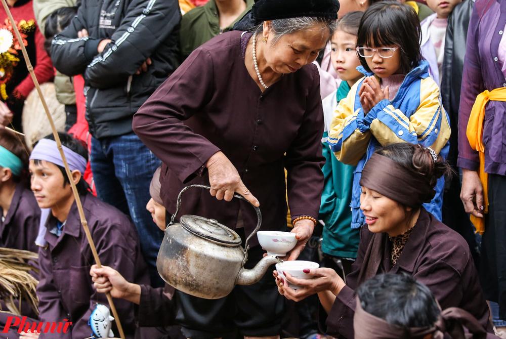 Một người cao tuổi rót những bát nước chè xanh thể hiện một hình ảnh nghỉ ngơi của người nông dân những năm xưa cũ. Đặc biệt, trong lễ hội này sẽ có nhiều anh nông dân do phụ nữ cải trang.