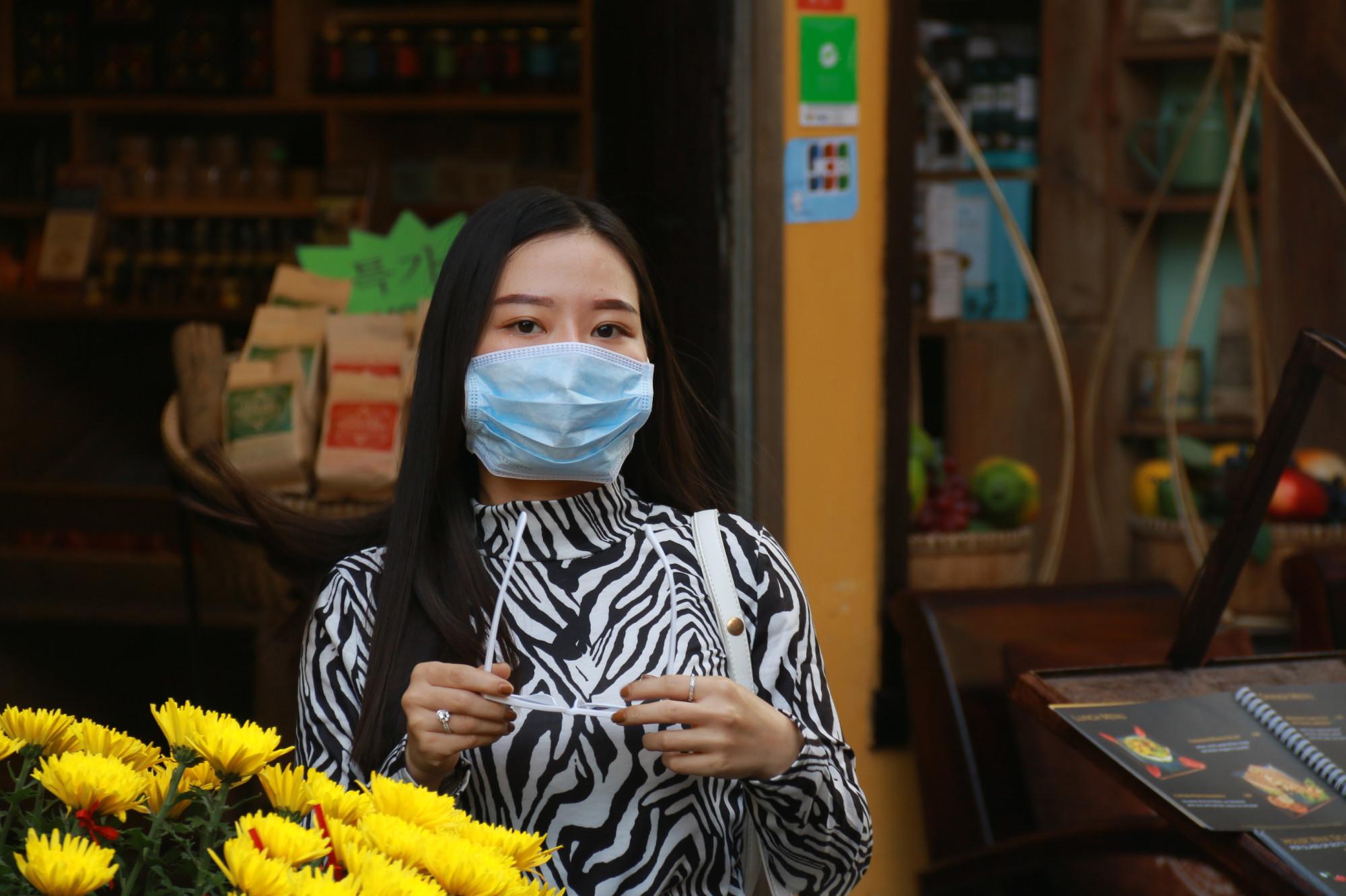 Một người phụ nữ chụp ảnh lưu niệm với khẩu trang bảo vệ mặt