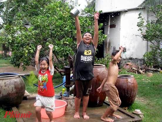 Sau khi chơi đùa thỏa thích, lũ trẻ sảng khoái khi được tắm nước lu mát lanh