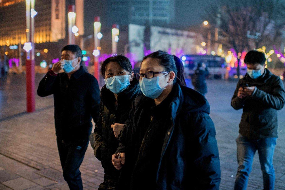Người đi bộ ở Bắc Kinh đeo khẩu trang y tế để tránh nhiễm 2019-nCoV - Ảnh: AFP
