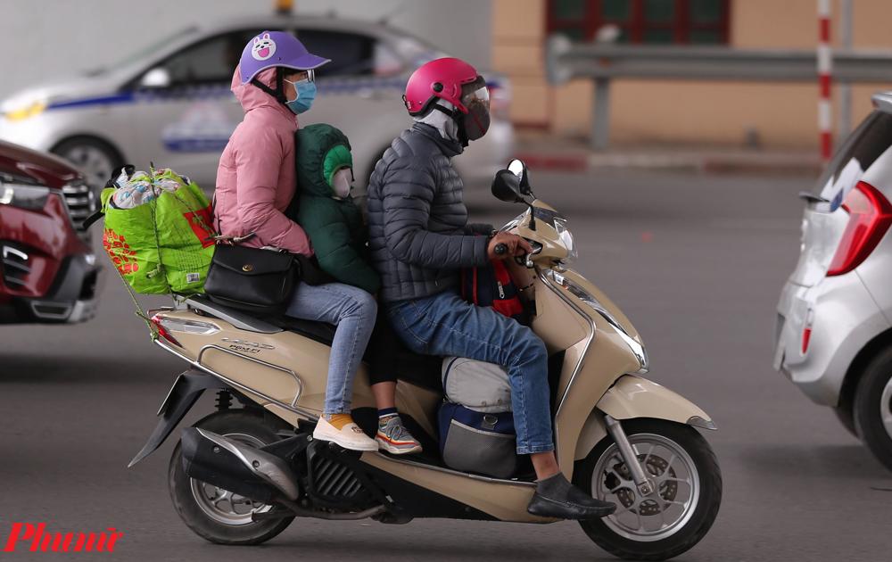Một gia đình di chuyển từ quê lên Hà Nội bằng xe máy.