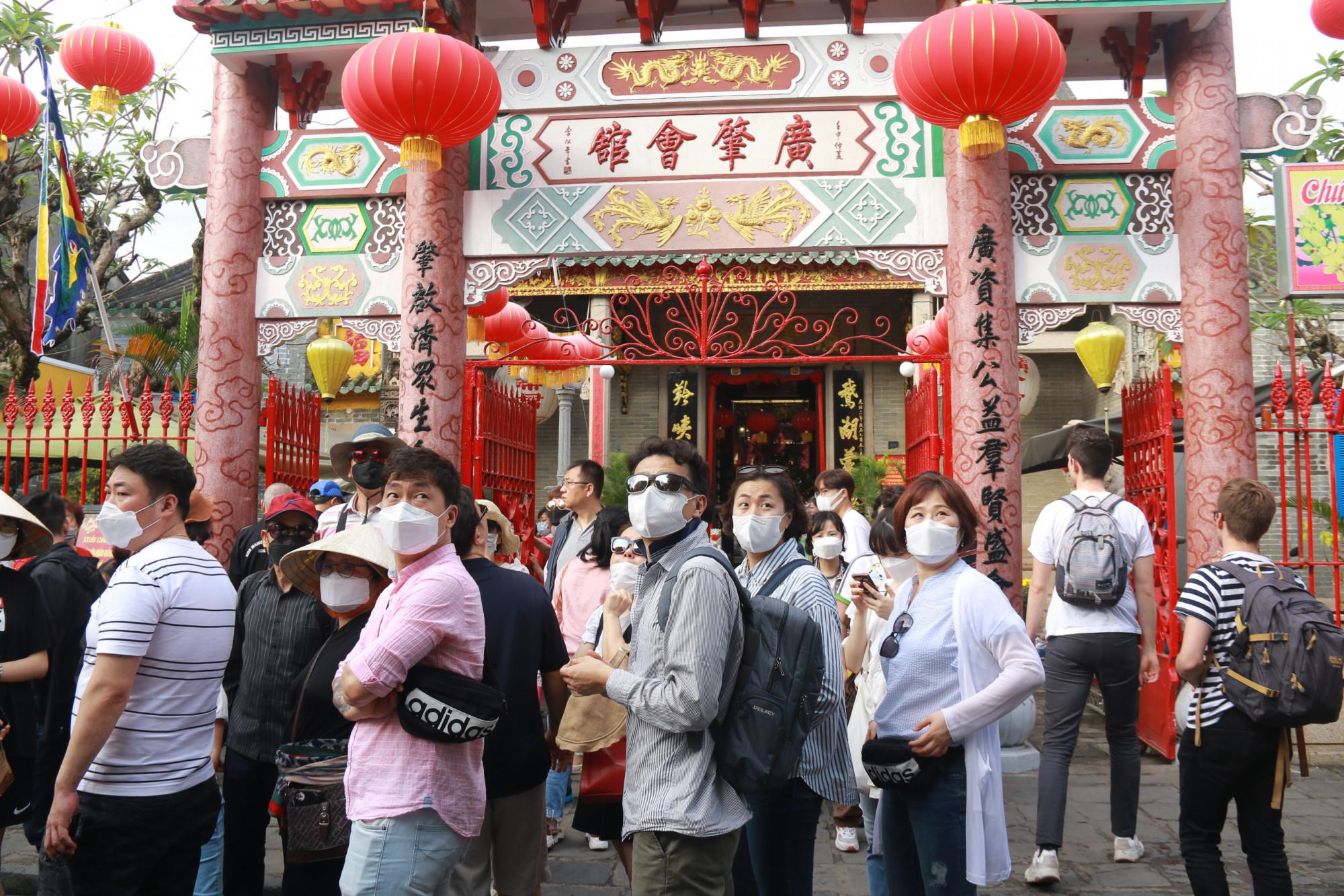 Khách du lịch tham quan trước một hội quán của người Trung Quốc ở Hội An