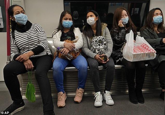 Hành khách trên một chuyến tàu điện tại Hồng Kông hôm 28/1.