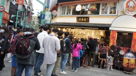 Xếp hàng trước một cửa hàng trà sữa nổi tiếng trên phố đi bộ