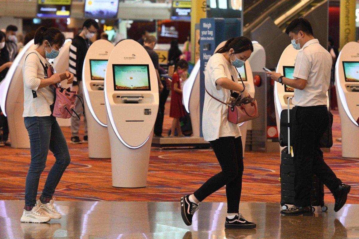 Du khách đeo khẩu trang tại sân bay quốc tế Changi ở Singapore - Ảnh: AFP