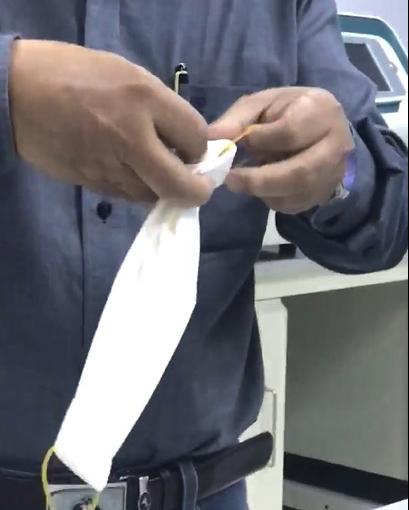 Bước 2: Thắt 4 sợi thun làm 2 phần, sau đó dùng bấm giấy kẹp giữ vào hai đầu khăn giấy đã xếp trước đó để làm dụng cụ đeo, ảnh cắt từ clip
