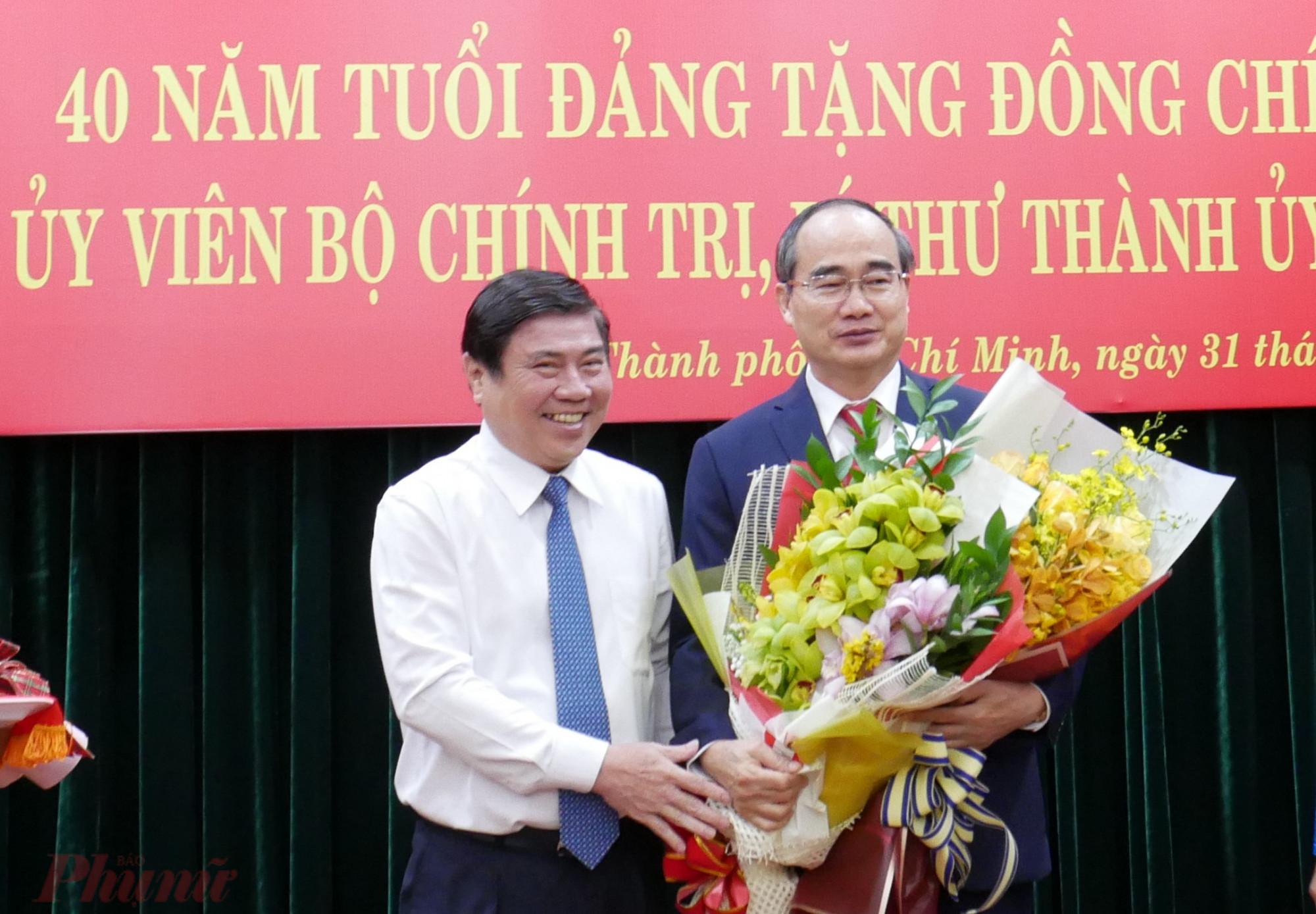 Chủ tịch UBND TPHCM Nguyễn Thành Phong tặng hoa chúc mừng Bí Thư Thành ủy nhân huy hiệu 40 năm tuổi Đảng.