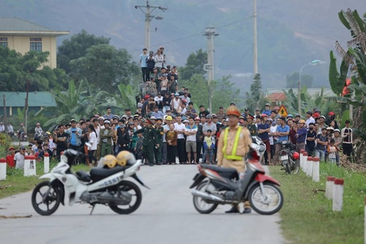 Đám đông dàn hàng ngang, chất chồng lên nhau để xem vây bắt tội phạm cố thủ có súng và lựu đạn.