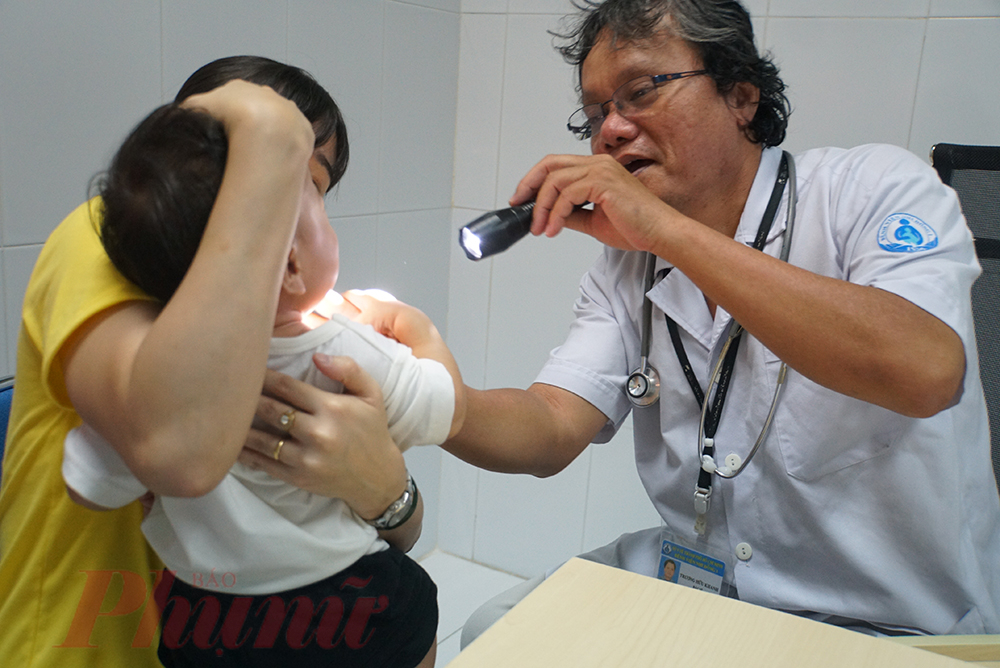 Bác sĩ Trương Hữu Khanh đang khám bệnh cho trẻ tại Bệnh viện Nhi Đồng 1.