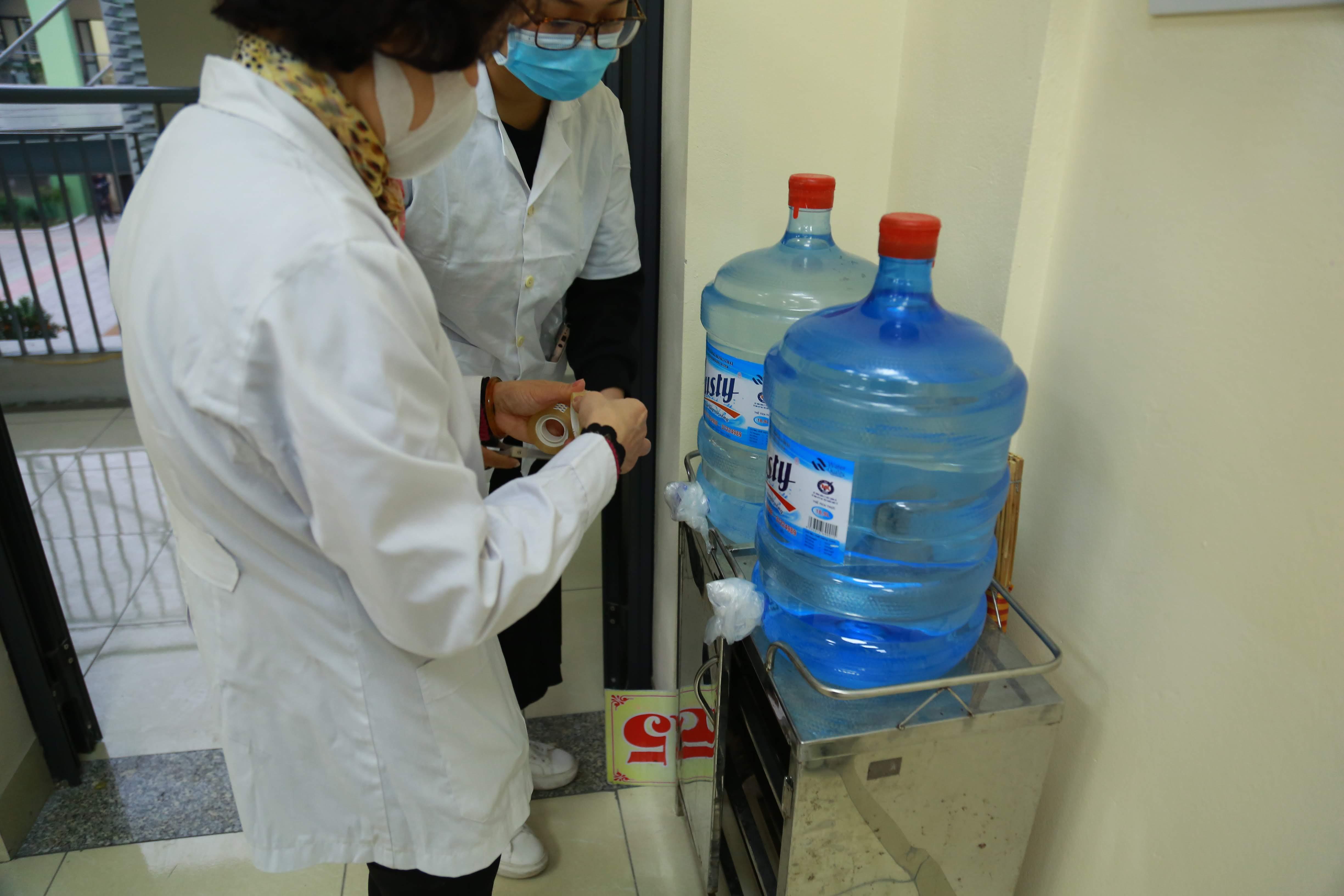 Cán bộ y tế cũng cẩn thận che chắn khu vực bình uống nước có trong trường.